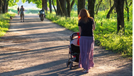 Woman pushing a stroller in the woods