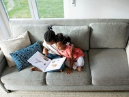 Young siblings reading together on a sofa