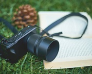 A camera rests on an open book on green grass.