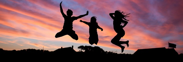 3 youth jumping silhouetted against a colourful sunset