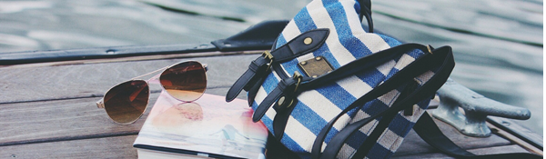 A bag, book and sunglasses resting on a lake side dock.