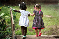 Two children holding hands crossing a bridge