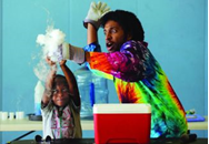 an adult and child wearing tie dye performing a science experiment