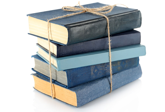 a stack of books with a cord around them, tied in a bow