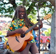photo of musician Asheba playing a guitar outside