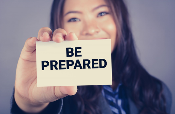 "Young woman holding up a card that says ""be prepared"""