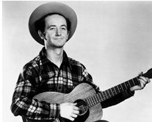 photo of young Woody Guthrie playing the guitar