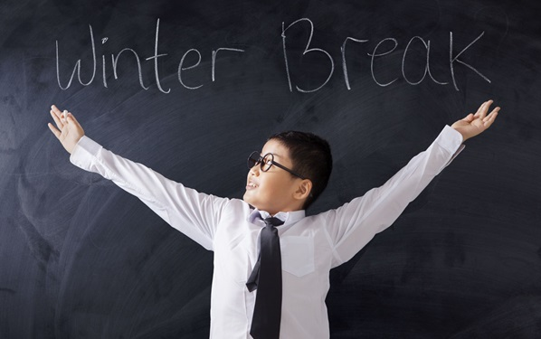 schoolage child with outspread hands in front of a chalkboard that says winter break
