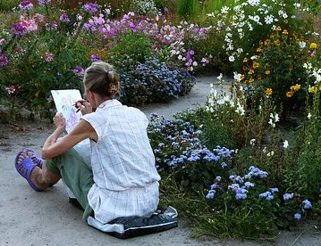 photo of a woman sitting on the ground in a journal sketching
