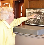 pic of patron pointing out where she grew up on an old map of Berkeley