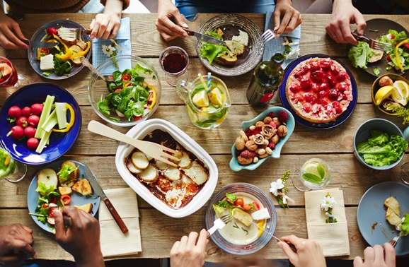 photo of a table filled with food and hands poised to eat