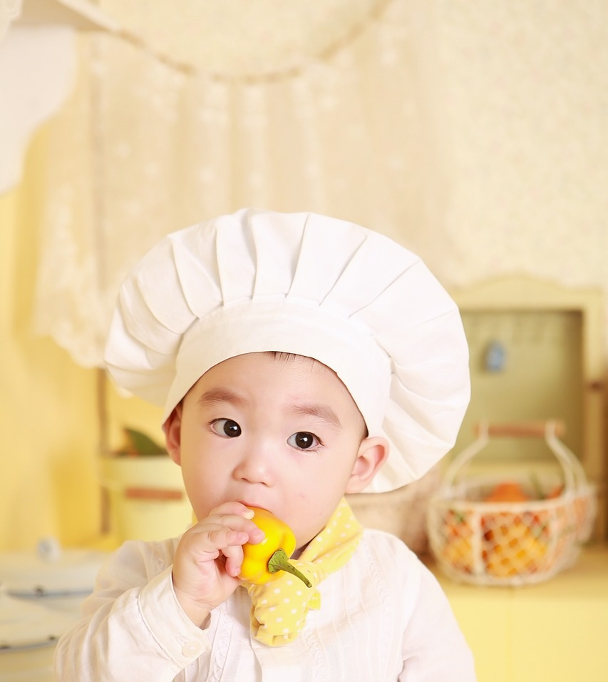A toddler dressed up as a chef