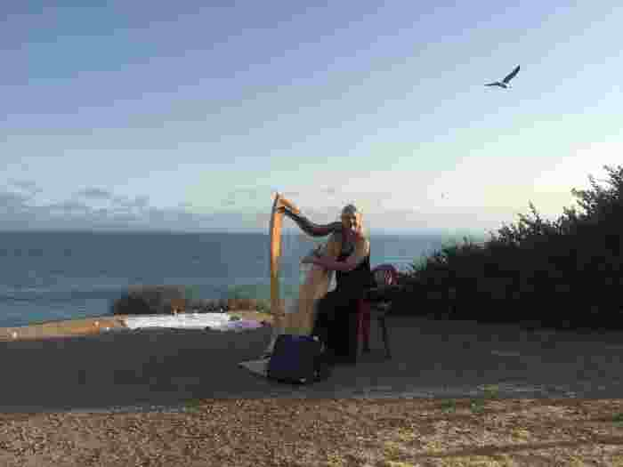 Peggy Skomal playing harp at the beach