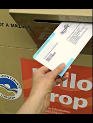 A hand places an election ballot in a ballot drop.