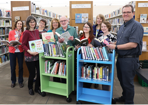 photo of library staff with two carts of books