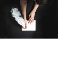 hands writing in notebook with feather quill
