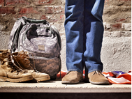 man's legs with backpack, boots, and American flag
