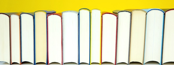 Books Lined Up on Yellow Background