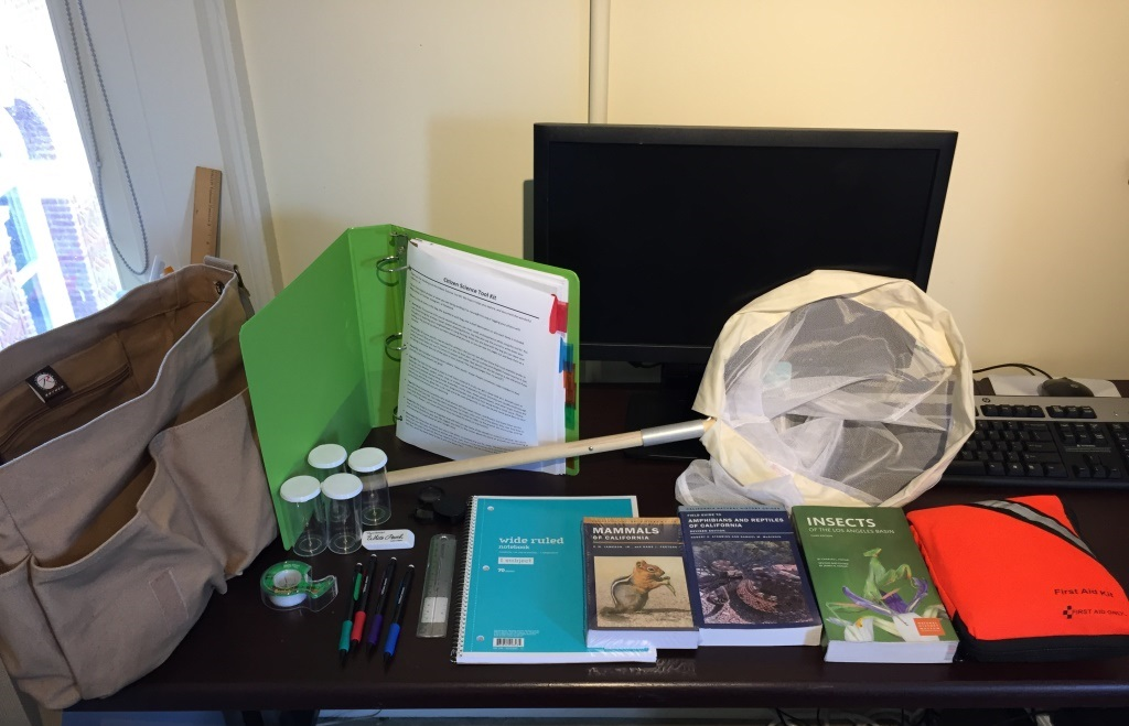 Various science items laid out a table like a net, binder folder, tape, notebooks, ruler, specimen bottles