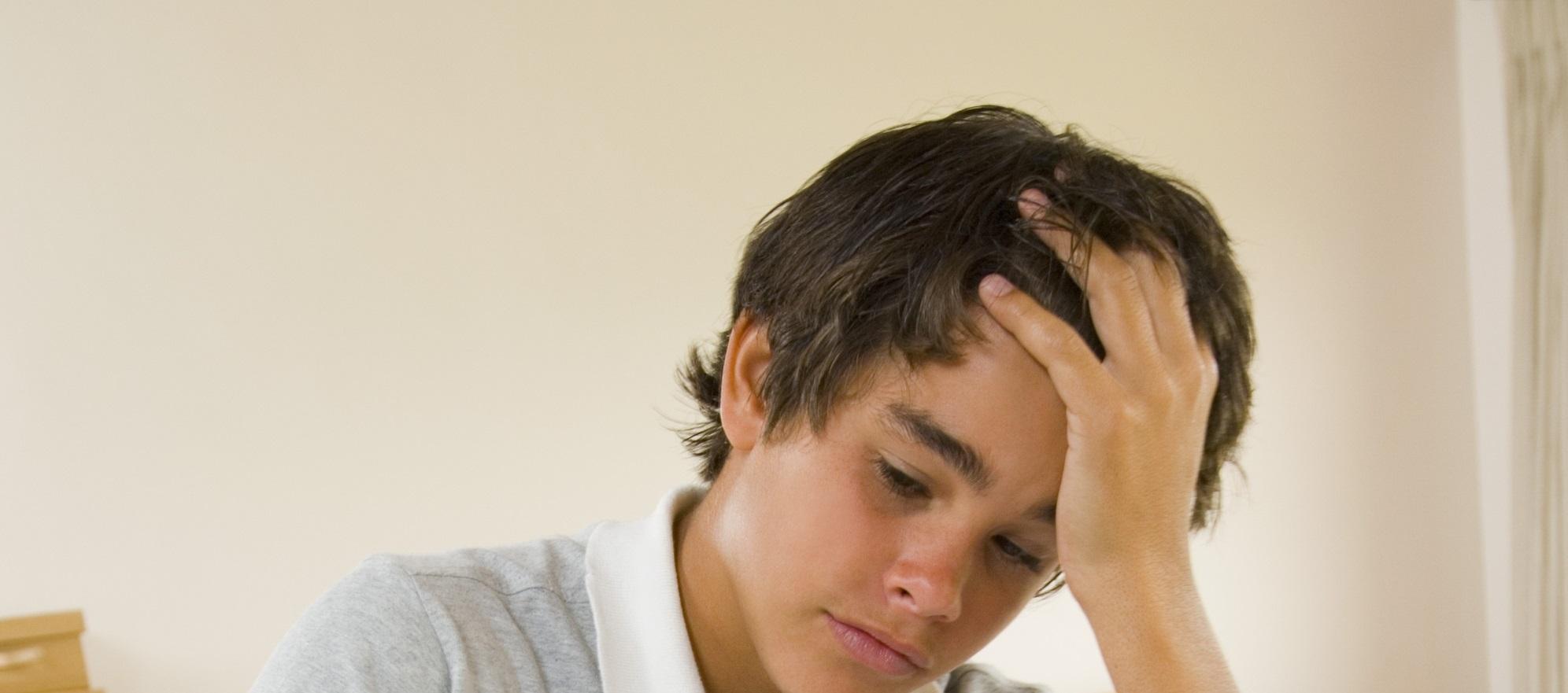 Teen doing homework, looking stressed