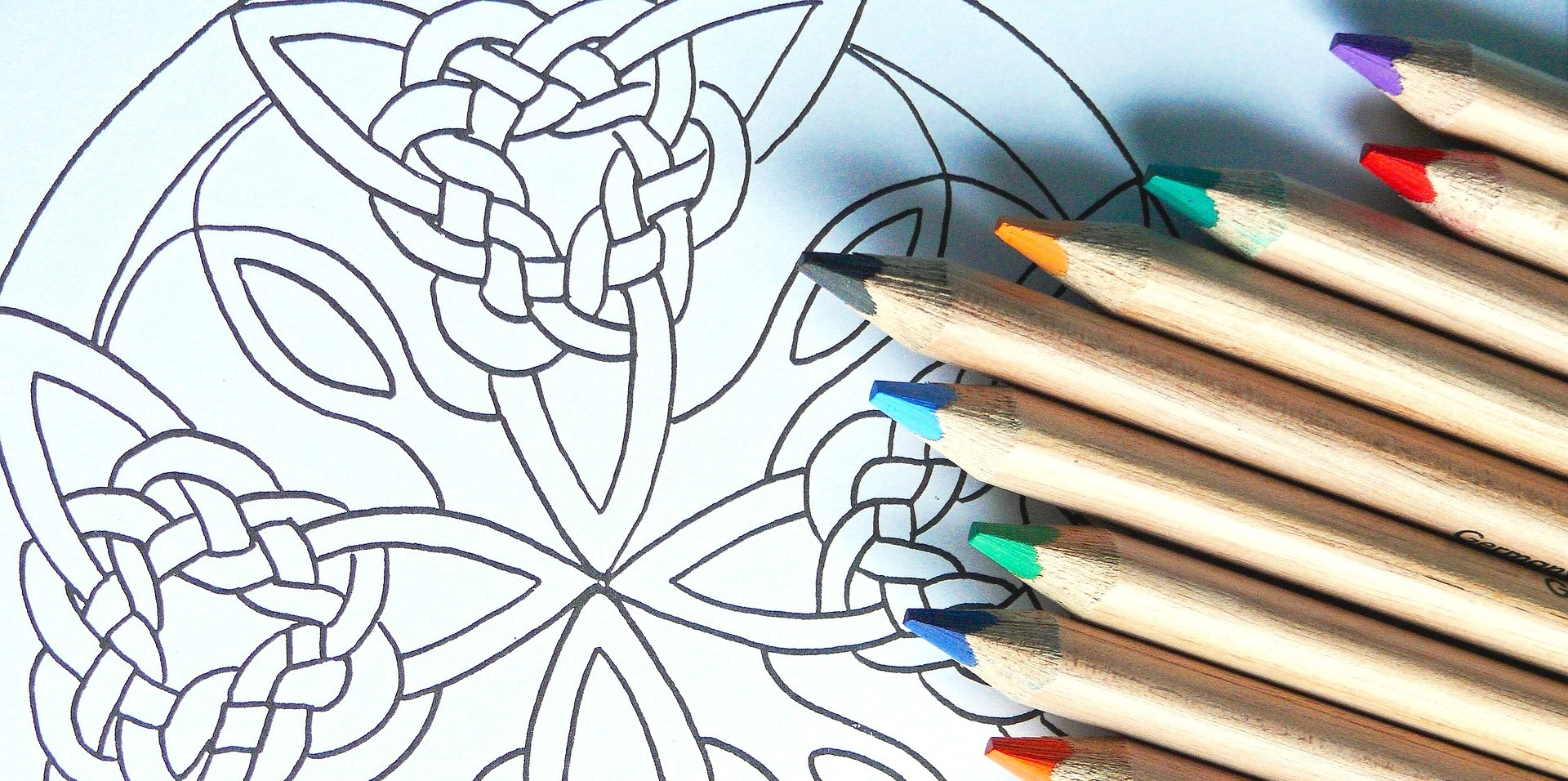 Colored pencils piled alongside a black and white outline of Celtic symbol