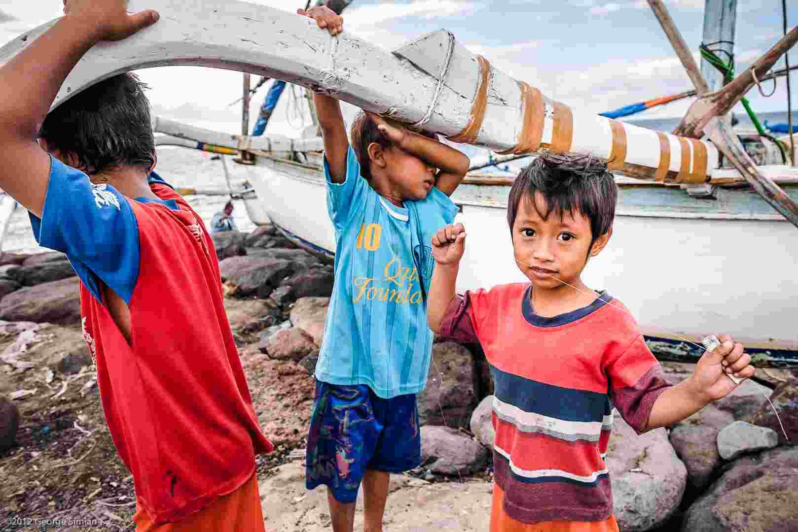 Three young boys hoist a small boat overhead on a rocky beach