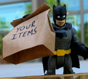 Toy batman holding a bag that says your items