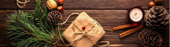 photo of pine bough, pine cones, candle, and wrapped present