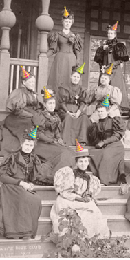 Vintage photo of Everett women's club members seated on porch stairs wearing added colorful party hats