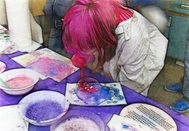 Photo of girl with pink hair leaning over blowing colored bubbles on paper